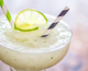 Frozen margarita cocktails with paper straws and lime garnish